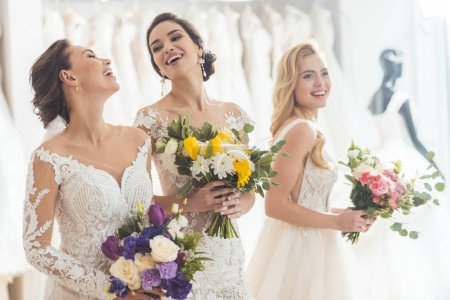 Happy women in wedding dresses with flowers in wedding atelier