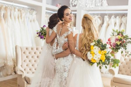 Brides in lace dresses with flowers in wedding atelier