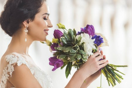 Young bride with flowers bouquet in wedding atelier
