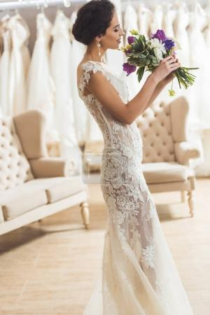 Beautiful bride with floral bouquet in wedding salon