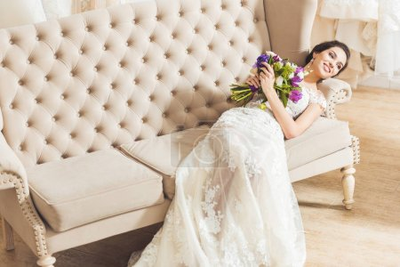 Photo for Young bride lying on sofa with flowers bouquet in wedding atelier - Royalty Free Image
