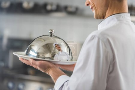 Photo for Cropped image of handsome chef holding plate with lid at restaurant kitchen - Royalty Free Image