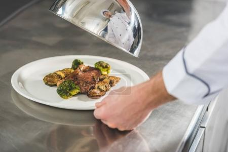 cropped image of chef holding plate with meal and lid at restaurant kitchen