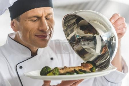handsome chef sniffing dish at restaurant kitchen with closed eyes