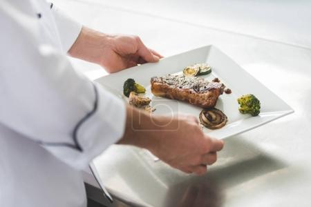 cropped image of chef holding plate with cooked steak and vegetables at restaurant kitchen