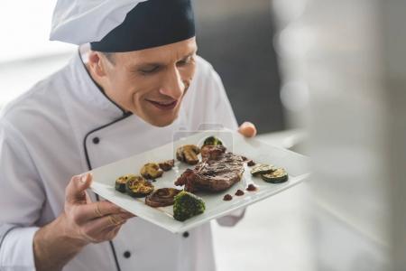 Photo pour Beau chef reniflant steak cuit avec des légumes au restaurant cuisine - image libre de droit