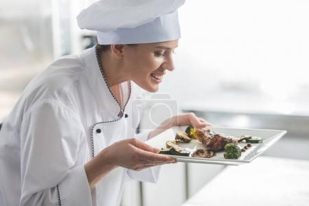 Photo for Attractive chef sniffing cooked steak at restaurant kitchen - Royalty Free Image