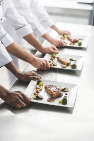cropped image of multiethnic chefs with plates with steaks at restaurant kitchen