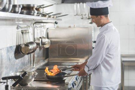 Photo pour Vue latérale du beau chef frire le steak avec le feu au restaurant de cuisine - image libre de droit