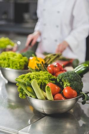 Photo for Cropped image of chef cooking at restaurant kitchen with vegetables on foreground - Royalty Free Image