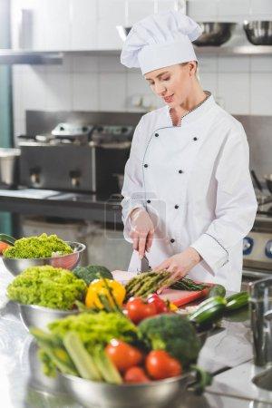 attractive chef cutting vegetables at restaurant kitchen