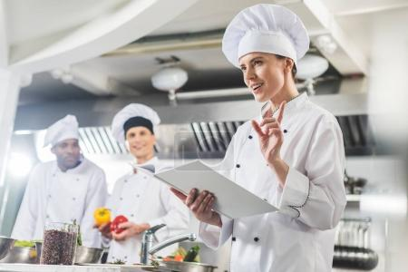 attractive chef holding recipe book and showing idea gesture at restaurant kitchen