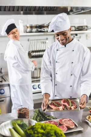 happy multicultural chefs cooking steaks at restaurant kitchen