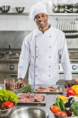 handsome african american chef looking at camera at restaurant kitchen