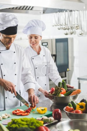 chef watching how colleague cutting vegetables at restaurant kitchen
