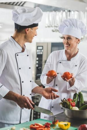 Photo for Smiling chef showing ripe tomatoes to colleague at restaurant kitchen - Royalty Free Image