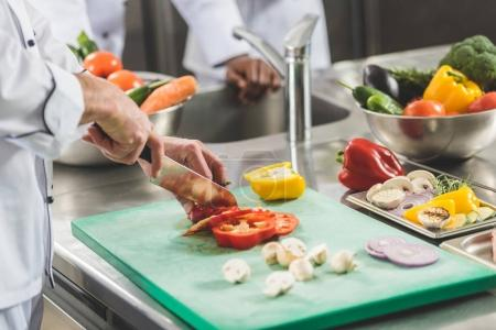 cropped image of chef cutting vegetables at restaurant kitchen