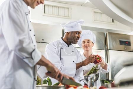 multicultural chefs preparing ripe vegetables at restaurant kitchen