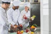smiling multicultural chefs preparing food at restaurant kitchen