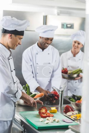 Photo for Happy multicultural chefs preparing vegetables at restaurant kitchen - Royalty Free Image