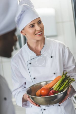 smiling chef holding bowl with vegetables and looking away at restaurant kitchen