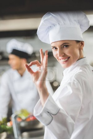 Photo for Smiling chef showing okay gesture at restaurant kitchen - Royalty Free Image