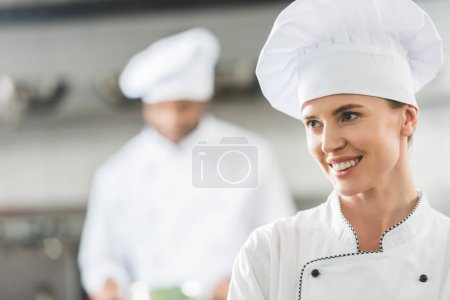 Photo for Smiling chef looking away at restaurant kitchen - Royalty Free Image