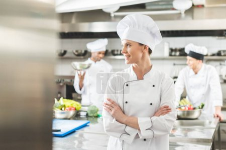 Photo for Smiling chef standing with crossed arms and looking away at restaurant kitchen - Royalty Free Image