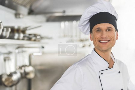 Photo for Happy handsome chef looking at camera at restaurant kitchen - Royalty Free Image