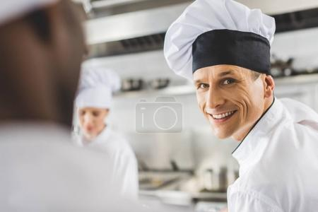 handsome smiling chef looking at camera at restaurant kitchen
