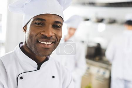 happy african american chef looking at camera at restaurant kitchen