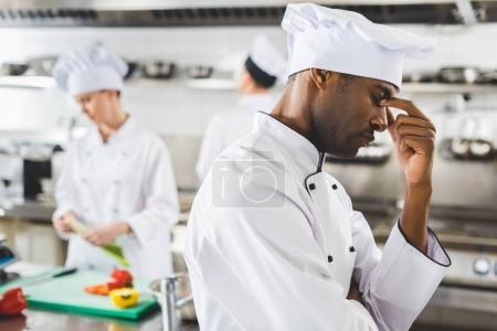 tired african american chef touching nose bridge at restaurant kitchen