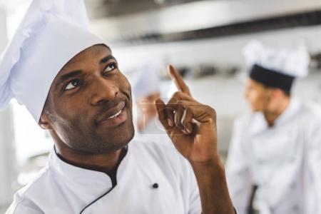 Photo pour Beau chef africain-américain pointant vers le haut à la cuisine du restaurant - image libre de droit