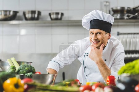Photo for Smiling pensive chef looking at camera at restaurant kitchen - Royalty Free Image