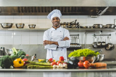 Photo for Handsome african american chef standing at restaurant kitchen with crossed arms and looking at camera - Royalty Free Image
