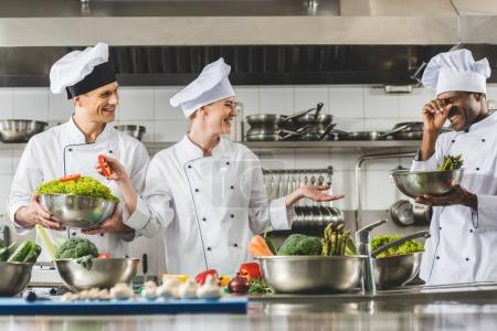 multicultural chefs laughing at restaurant kitchen