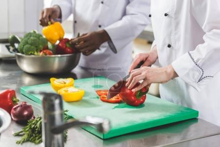 cropped image of chef cutting bell peppers at restaurant kitchen