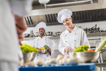 smiling multicultural chefs preparing food at restaurant kitchen and looking at camera