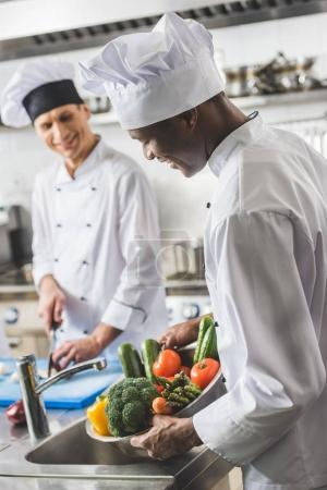 african american chef washing vegetables at restaurant kitchen