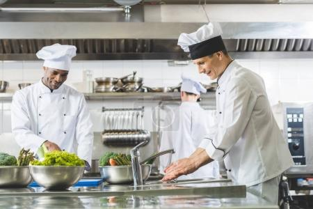 Photo for Multicultural chefs working at restaurant kitchen - Royalty Free Image