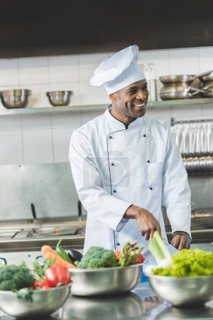 smiling handsome african american chef cutting vegetables at restaurant kitchen