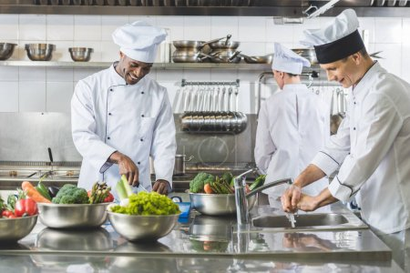 Photo for Multicultural chefs cooking at restaurant kitchen - Royalty Free Image