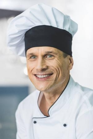 portrait of smiling handsome chef at restaurant kitchen