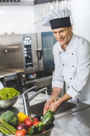 handsome chef washing hands at restaurant kitchen