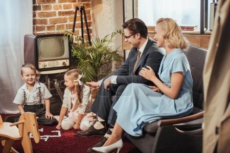 Photo pour Heureux des années 50 style parents assis sur le canapé et regarder adorables enfants qui jouent à la maison - image libre de droit