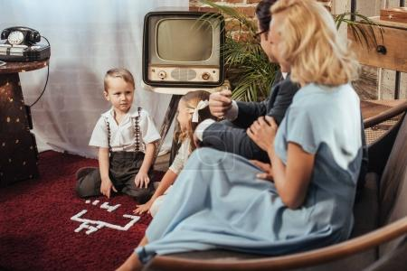parents sitting on sofa and looking at adorable children playing at home, 50s style
