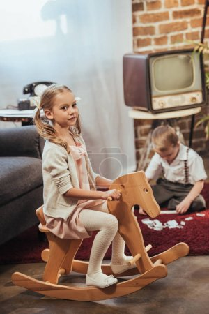 Photo for Girl sitting on rocking horse and looking at camera and little brother playing with domino tiles behind at home, 1950s style - Royalty Free Image