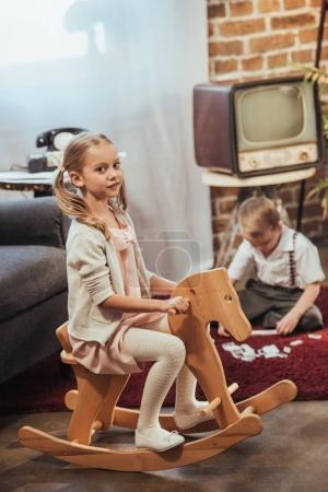 Photo pour Fille assise sur le cheval à bascule et regardant caméra et petit frère joue avec domino tuiles derrière à la maison, de style années 1950 - image libre de droit