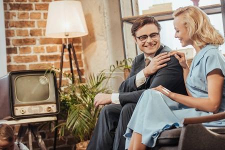 Photo pour 50 ans heureux couple style assis sur le canapé et l'autre souriant - image libre de droit