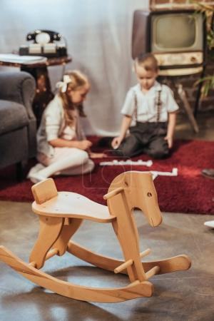 wooden rocking horse and little kids playing with domino tiles at home, 50s style
